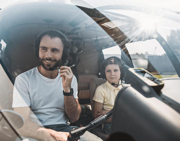dad and son sitting in helicopter