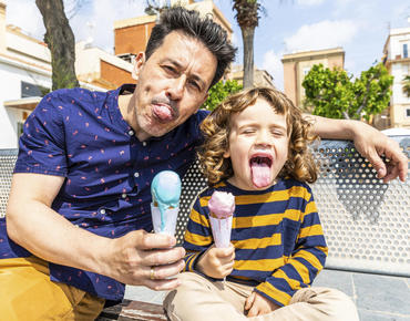 dad and song holding ice cream cones and sticking tongues out