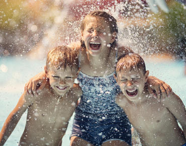 three kids with arms around each other's shoulders under fountain at water park