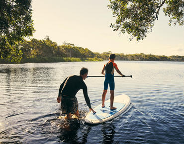 dad helping son stand up paddleboard in lake