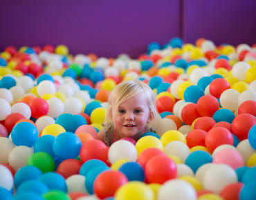 little blonde girl sitting in ball pit