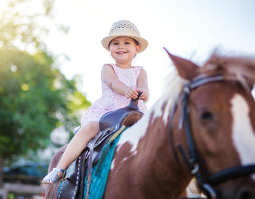 young girl riding brown and white horse