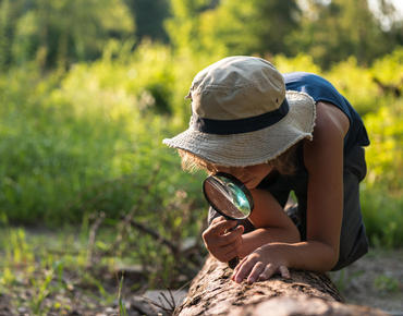 girl looking at log with magnifying glass