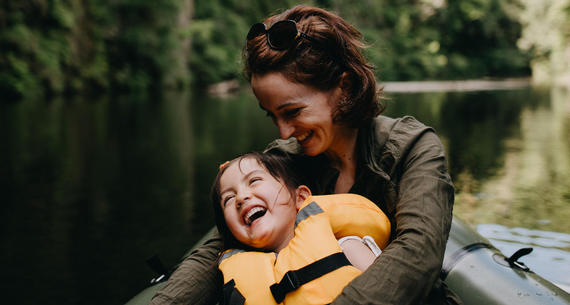 mom holding daughter laughing in kayak
