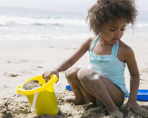 young girl in blue bathing suit holding yellow bucket sitting on the sand