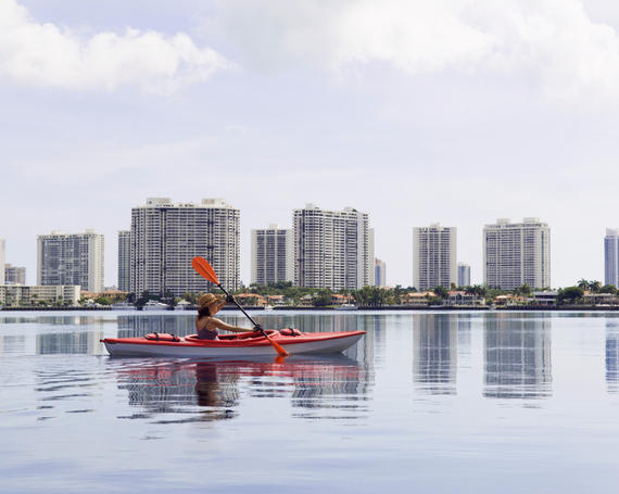 woman paddling kayak in still water with sunny isles beach