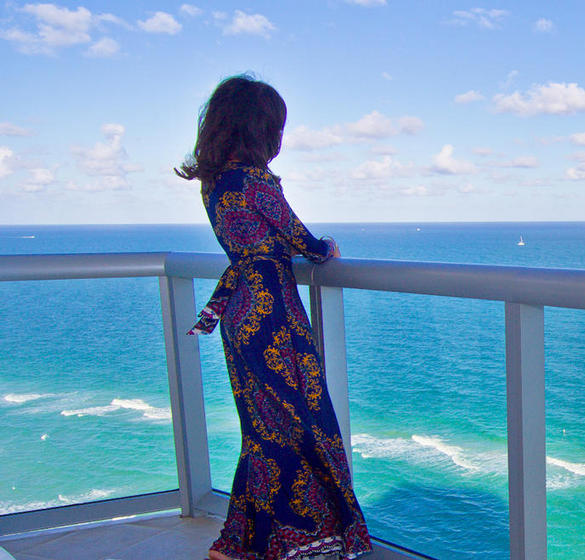 Lady on balcony overlooking the ocean